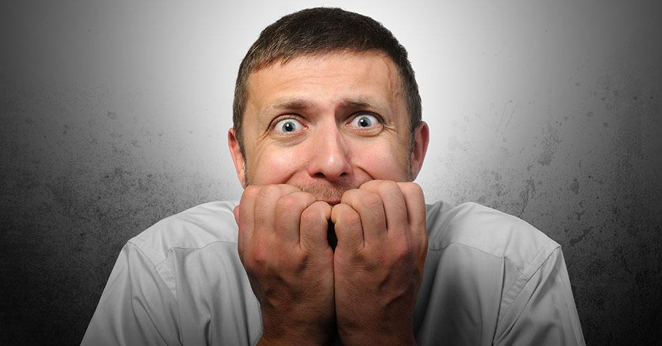 10 dicas para falar bem em público e superar o medo! A imagem mostra um homem ansioso roendo as unhas.
